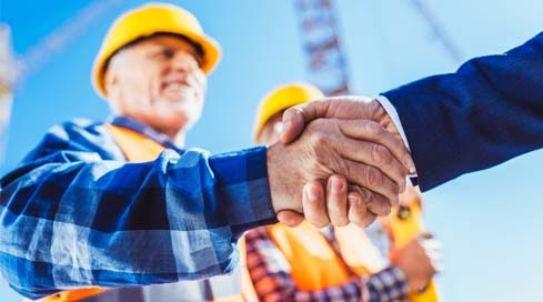 Construction finance manager shakes hands with a business partner on the job site