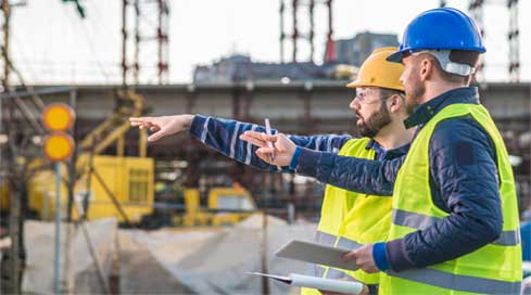 Two construction managers discussing project management on a construction site.