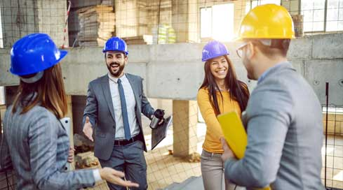 happy project managers shaking hands on job site